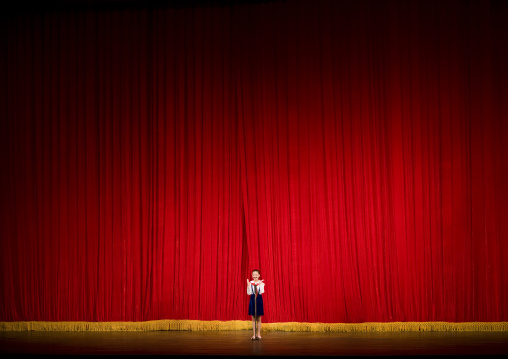 North Korean girl in front of a red curtain on the stage of Mangyongdae theatre, Pyongan Province, Pyongyang, North Korea