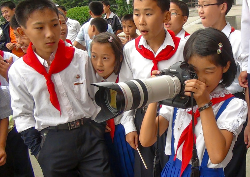 Pionner girl taking picture with a canon camera and a huge zoom, Kangwon Province, Wonsan, North Korea
