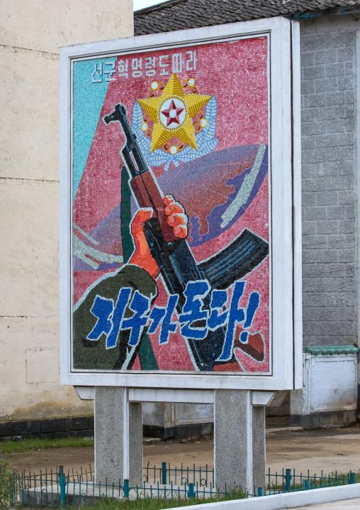 Propaganda billboard and a slogan saying planet turns according to songun revolutionary leadership, South Hamgyong Province, Hamhung, North Korea