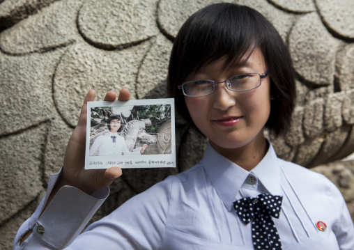 North Korean young woman showing a polaroid of herself, Pyongan Province, Pyongyang, North Korea