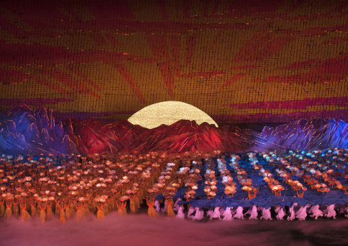 North Korean dancers in front of rising sun over mount Paektu made by children holding up boards during Arirang mass games in may day stadium, Pyongan Province, Pyongyang, North Korea