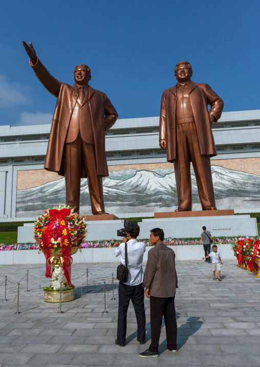 North Korean cameraman in front of the statues of the Dear Leaders in Mansudae Grand monument, Pyongan Province, Pyongyang, North Korea