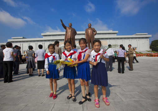 North Korean pioneers girls from the Korean children's union in front of the two statues of the Dear Leaders in the Grand monument on Mansu hill, Pyongan Province, Pyongyang, North Korea