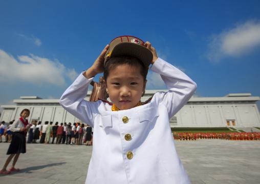 North Korean boy in army uniform putting his kepi in Grand monument of Mansu hill, Pyongan Province, Pyongyang, North Korea