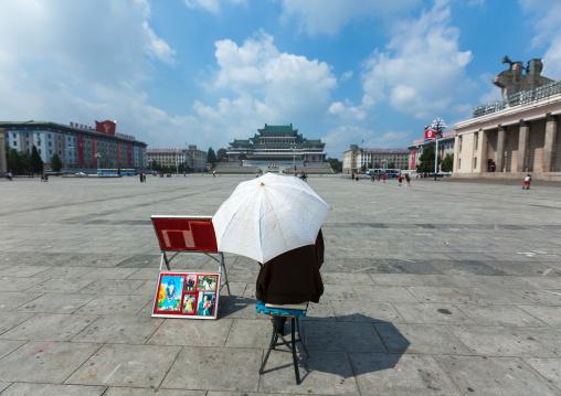 North Korean photographer waiting under an umbrella in Kim il Sung square, Pyongan Province, Pyongyang, North Korea