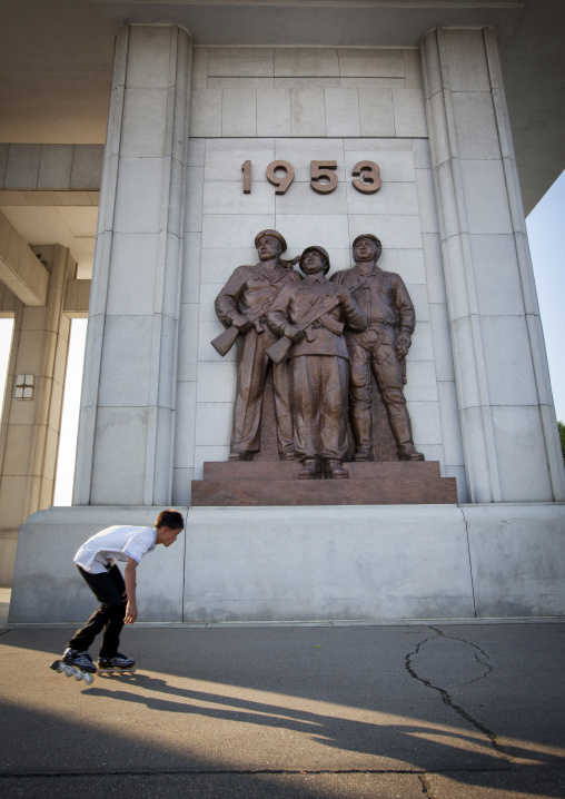 North Korean teenage boy roller skating in front of monument to the victorious fatherland liberation war museum, Pyongan Province, Pyongyang, North Korea