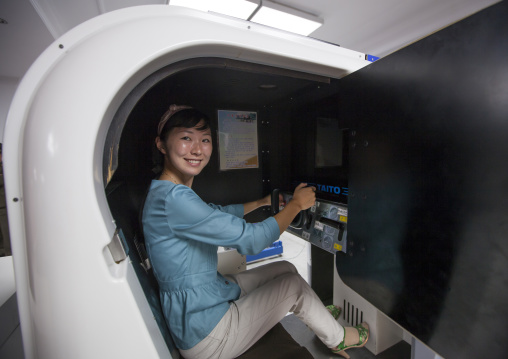 North Korean woman on a car simulator in Kaeson youth park, Pyongan Province, Pyongyang, North Korea