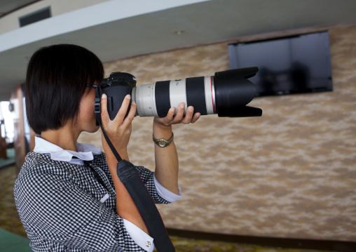 North Korean woman testing a professional camera, Pyongan Province, Pyongyang, North Korea