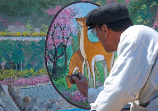North Korean artist painting a propaganda wall in the countryside, North Hamgyong Province, Chilbo Sea, North Korea