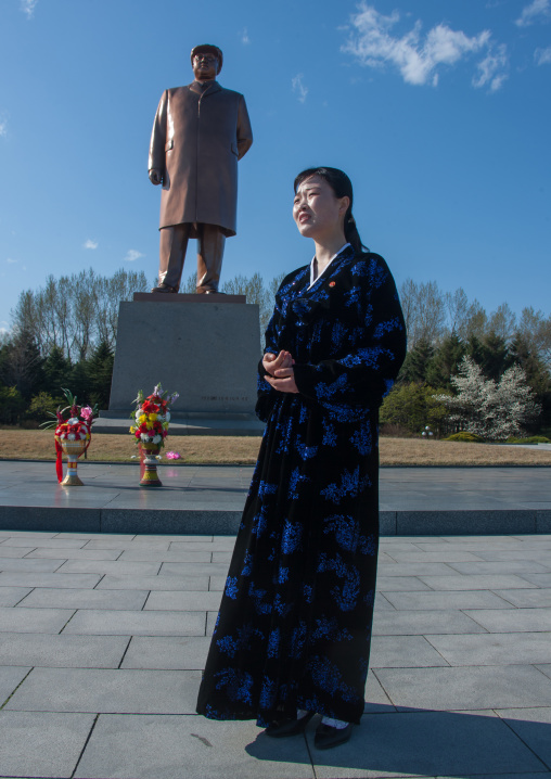 North Korean woman in front of Dear leader Kim il Sung statue on main square, North Hamgyong Province, Chongjin, North Korea