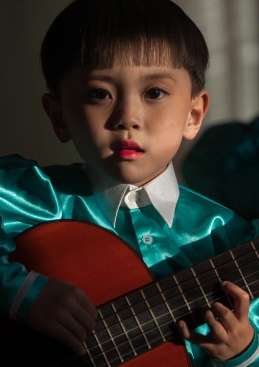 North Korean boy playing guitar in Tchang Gwang school, North Hamgyong Province, Chongjin, North Korea
