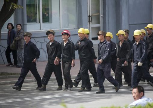North Korean workers with yellow helmets walking in the street, Pyongan Province, Pyongyang, North Korea