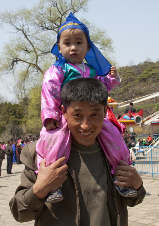 North Korean father carrying his one year old son in traditional clothing on his shoulders, Pyongan Province, Pyongyang, North Korea