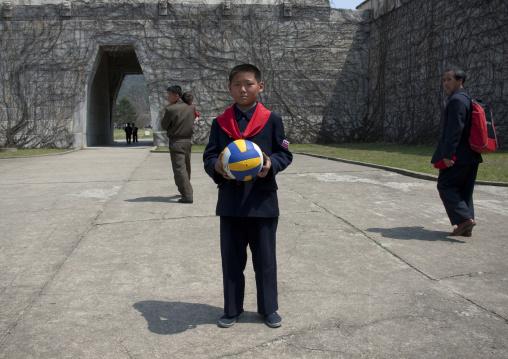 North Korean pioneer holding a ball in his hands, Pyongan Province, Pyongyang, North Korea