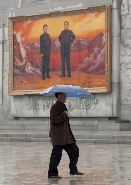 North Korean man with an umbrella in front of a fresco with the Dear Leaders posing on mount Paektu, Pyongan Province, Pyongyang, North Korea