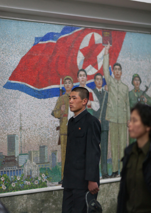 North Korean people in the subway in front of a propaganda mosaic, Pyongan Province, Pyongyang, North Korea