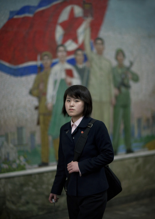 North Korean young woman in the subway in front of a propaganda mosaic, Pyongan Province, Pyongyang, North Korea