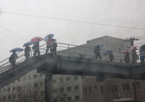 North Korean pedestrians crossing a bridge under the rain, Pyongan Province, Pyongyang, North Korea
