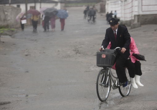 North Korean student giving a lift to a woman on his bicycle, North Hwanghae Province, Kaesong, North Korea