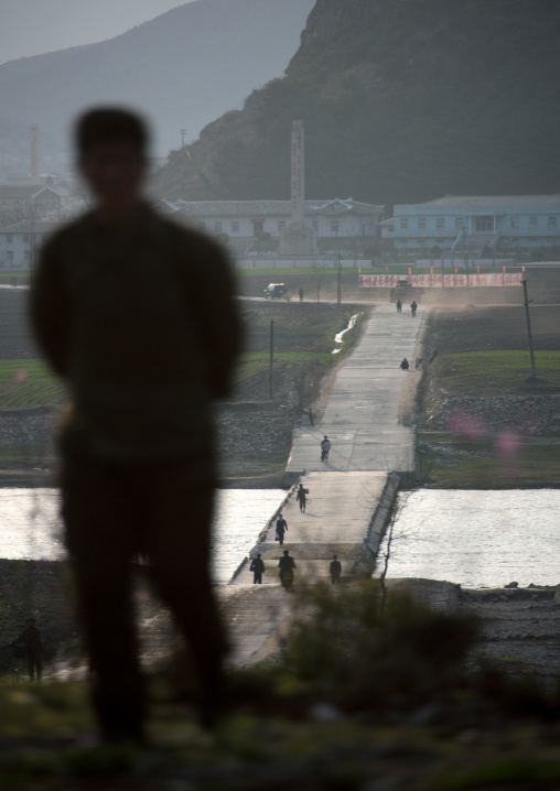 North Korean man overlooking a small bridge on a river, Kangwon Province, Wonsan, North Korea