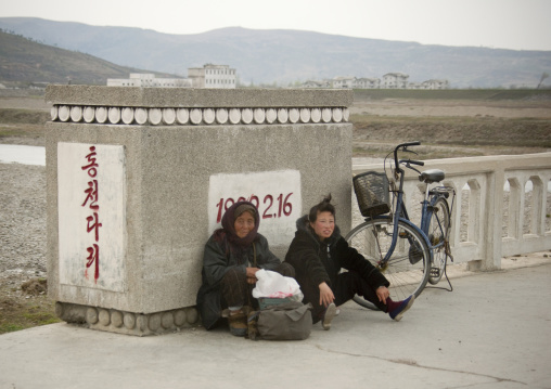 North Korean women leaning on a bridge in the countryside, Kangwon Province, Wonsan, North Korea