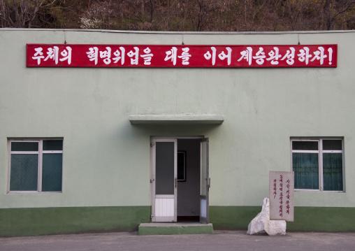 Propaganda slogan above the entrance of a building saying let us accomplish the succession by continuing the great revolutionary success of juche!, Ryanggang Province, Samjiyon, North Korea