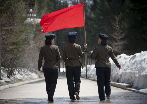 North Korean students with a red flag walking on the steps of the nation's heroes in mount Paektu, Ryanggang Province, Samjiyon, North Korea