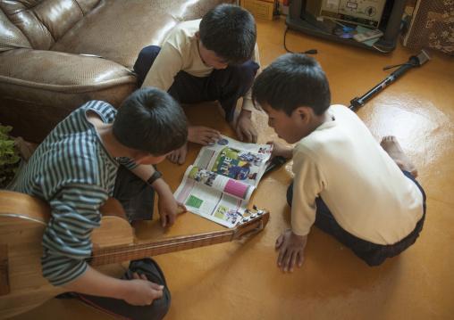 North Korean twins reading a western football magazine, North Hamgyong Province, Jung Pyong Ri, North Korea