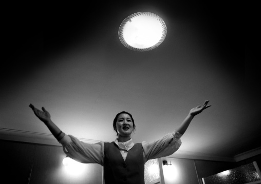 North Korean waitress singing in restaurant under halo light, Pyongan Province, Pyongyang, North Korea