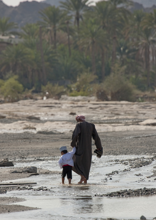 Figure Of Man Walking In The Water With A Kid, Sinaw, Oman