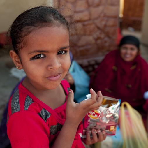 Bedouin Little Girl Holding A Pack Of Crisps, Ibra, Oman