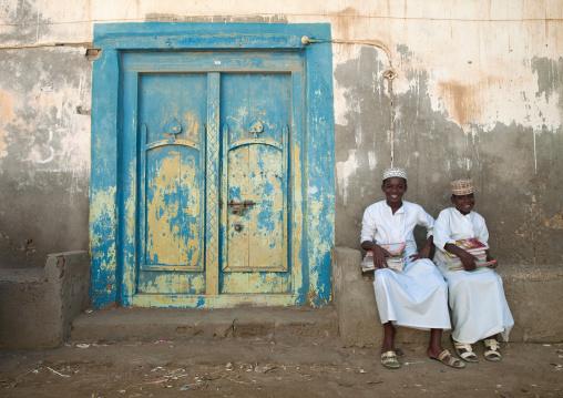 Two Kids In White Dishdasha Sitting Next To A Blue Wooden Door, Mirbat, Oman