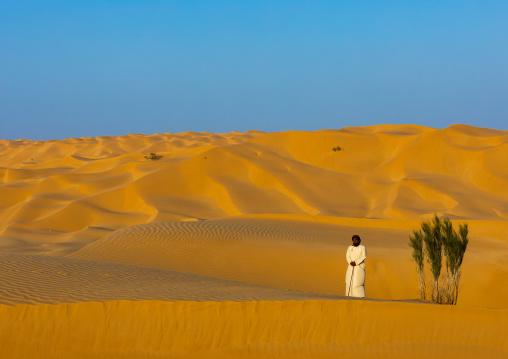 Omani man standing near a tree in the rub al khali desert, Dhofar Governorate, Rub al Khali, Oman