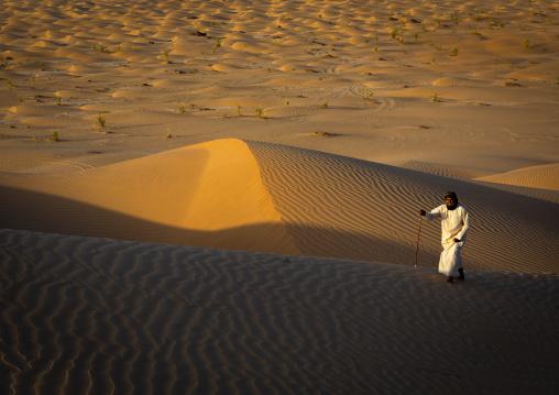 Omani man walking in the rub al khali desert, Dhofar Governorate, Rub al Khali, Oman