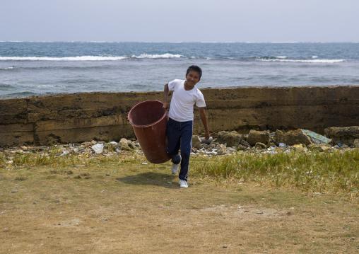 Panama, San Blas Islands, Mamitupu, Kuna Boy Collecting Garbage In A School