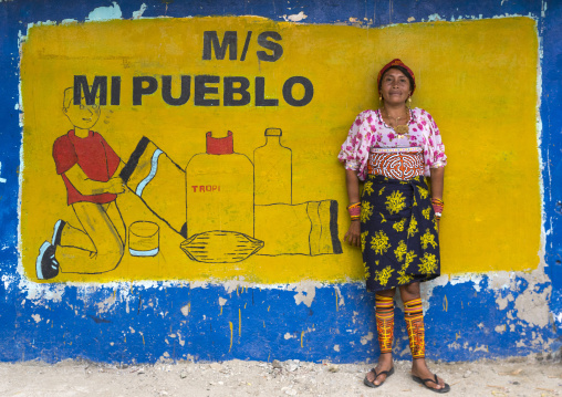 Panama, San Blas Islands, Mamitupu, Kuna Tribe Woman In Front Of An Advertising