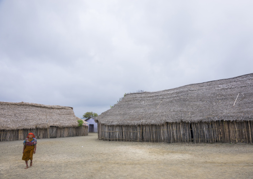Panama, San Blas Islands, Mamitupu, Kuna Indian Woman Pssing In Front Of Typical Homes With Thatched Roofs
