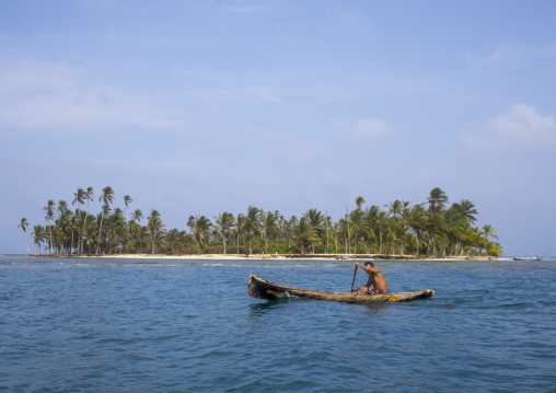 Panama, San Blas Islands, Mamitupu, Kuna Indian Man In A Traditional Canoe In Front Of An Island