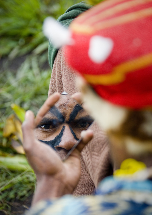 Warrior looking at himself in a mirror before a Sing-sing, Western Highlands Province, Mount Hagen, Papua New Guinea