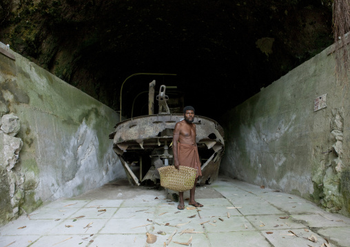 Man inside karavia tunnel in front of a boat wreck, East New Britain Province, Rabaul, Papua New Guinea
