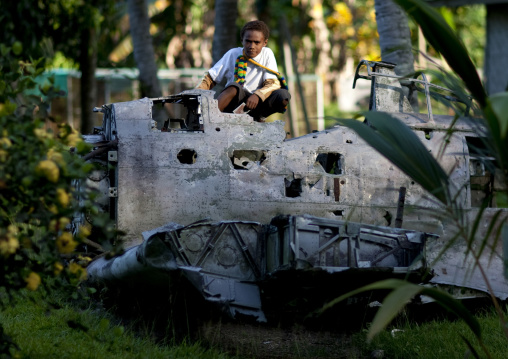 Boy sit on a plane wrecks in the war museum garden, East New Britain Province, Rabaul, Papua New Guinea