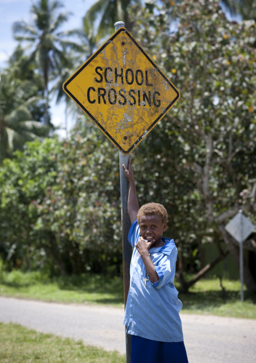 Boy standing in front of a road sign for a school, East New Britain Province, Rabaul, Papua New Guinea