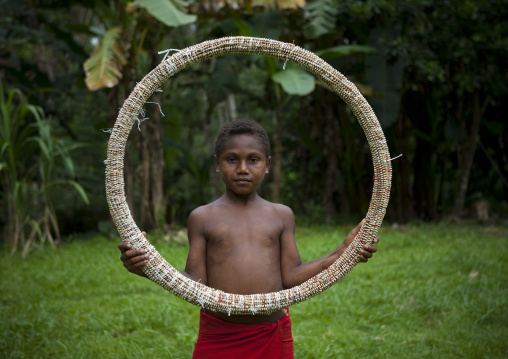Boy holding a giant traditional shell money, East New Britain Province, Rabaul, Papua New Guinea