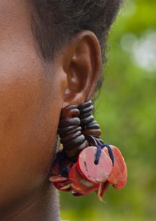 Little girl wearing earrings made with turtle shell, Milne Bay Province, Trobriand Island, Papua New Guinea