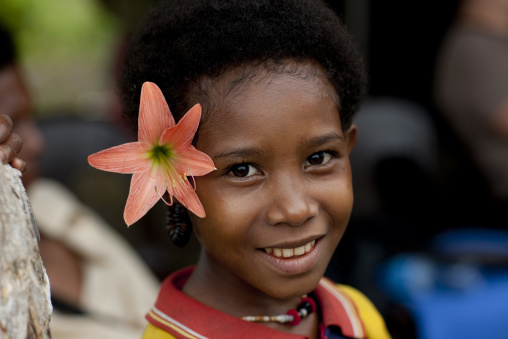 Smiling girl with flowers in the hair, Milne Bay Province, Trobriand Island, Papua New Guinea