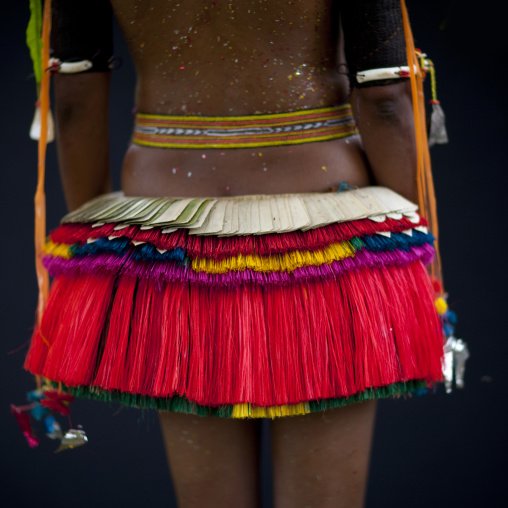 Woman wearing a traditional red skirt made with pandanus and banana leaves, Milne Bay Province, Trobriand Island, Papua New Guinea