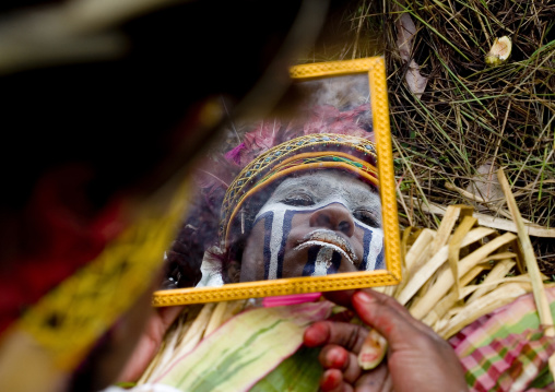 Melpa tribe woman looking in a mirror during a sing sing, Western Highlands Province, Mount Hagen, Papua New Guinea