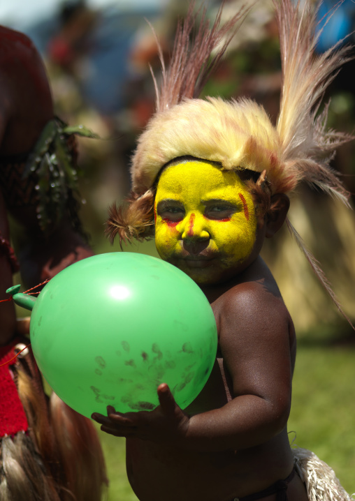 Portrait of a Huli tribe boy with a baloon during a sing-sing, Western Highlands Province, Mount Hagen, Papua New Guinea