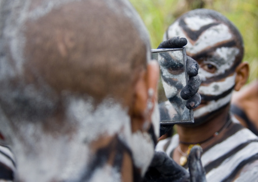 Snake man during a sing sing looking at himself in a mirror, Western Highlands Province, Mount Hagen, Papua New Guinea