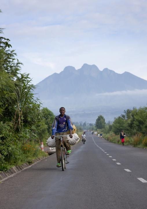 Rwandan man riding a bicycle on the road leading to the volcano, Northwest Province, Rehengeri, Rwanda